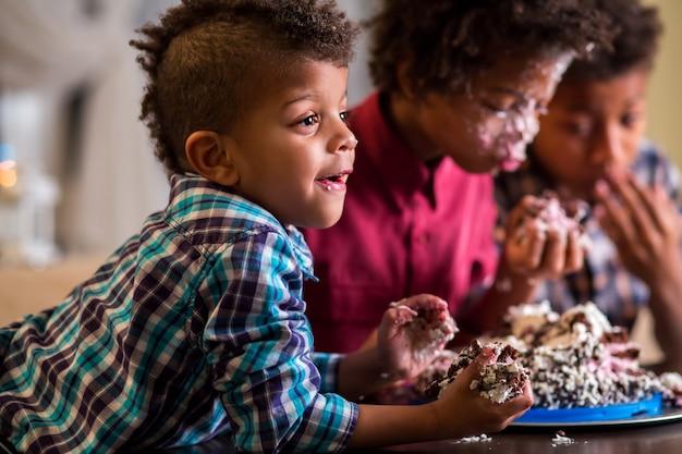 Dzieci jedzą ciasto rękami.
