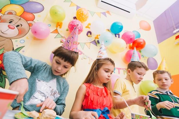 Dzieci jedzą na przyjęciu urodzinowym