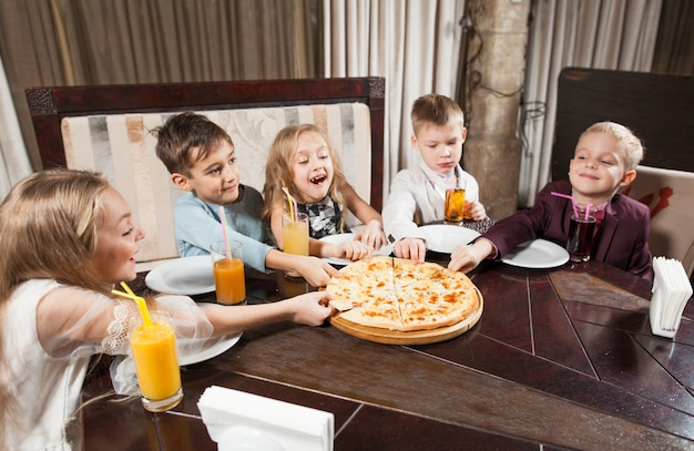 Dzieci jedzą pizzę w restauracji.