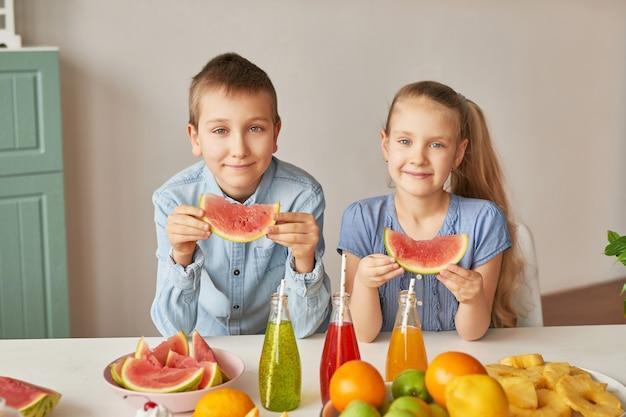 Dzieci jedzą plastry arbuza w kuchni