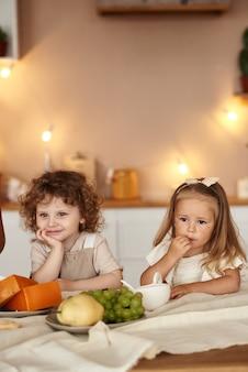 Dzieci jedzą śniadanie owocowe w kuchni rano.