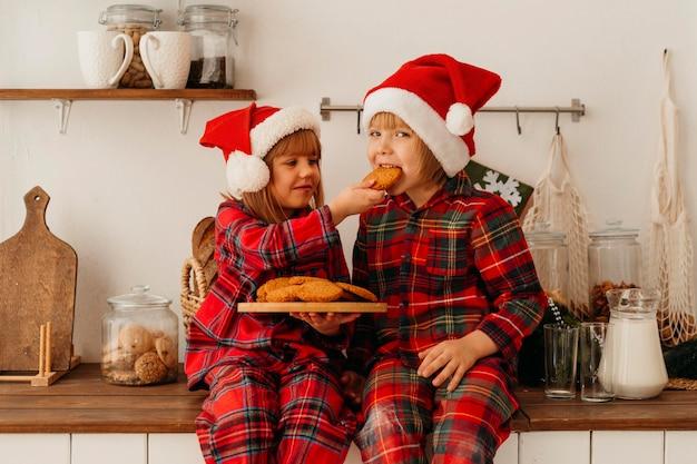 Dzieci jedzą świąteczne ciasteczka