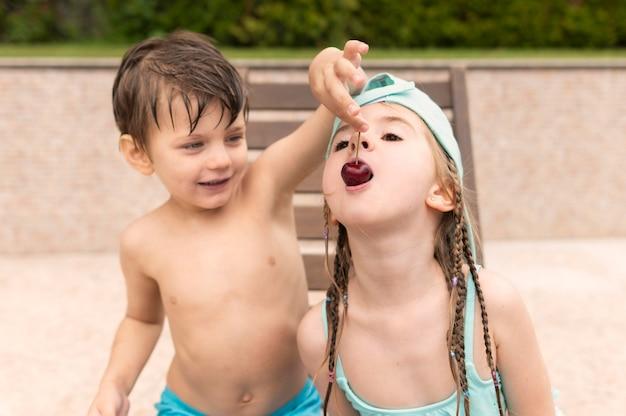 Dzieci jedzą wiśnie przy basenie