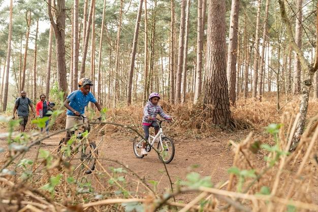 Dzieci jeżdżące na rowerze po lesie