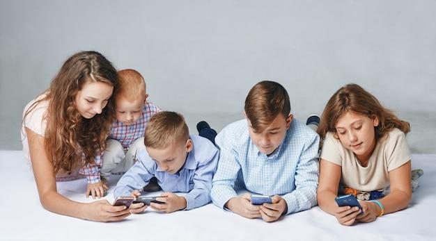 Dzieci koncentrują się na graniu w smartfony