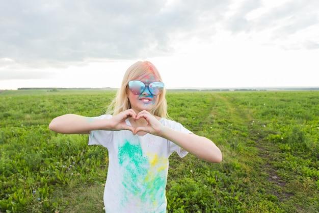 Dzieci, koncepcja festiwalu holi i wakacji - szczęśliwa mała dziewczynka pokryta kolorowym proszkiem