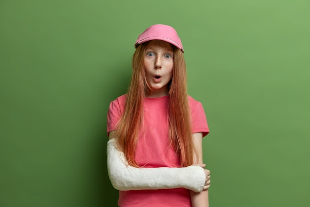 Dzieci, koncepcja wyrażeń twarzy. zaskoczona piegowata dziewczyna wygląda ze zdziwieniem, ma złamaną rękę w gipsie, nosi różową czapkę i koszulkę, odizolowana na zielonej ścianie, spadła z roweru