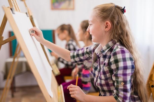 Dzieci korzystają ze sztalugi w szkole artystycznej.
