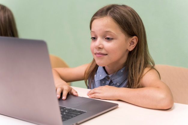 Dzieci korzystające z laptopa w szkole