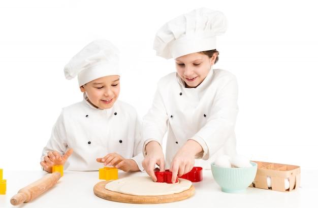 Dzieci-kucharze bawią się w formy do cięcia ciasta