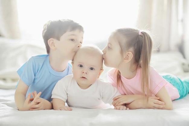 Dzieci leżą na łóżku obok noworodka, siostrzyczko. emocje dzieci.