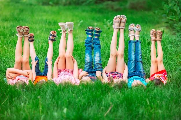 Dzieci leżące na zielonej trawie w parku w letni dzień z nogami uniesionymi do nieba.