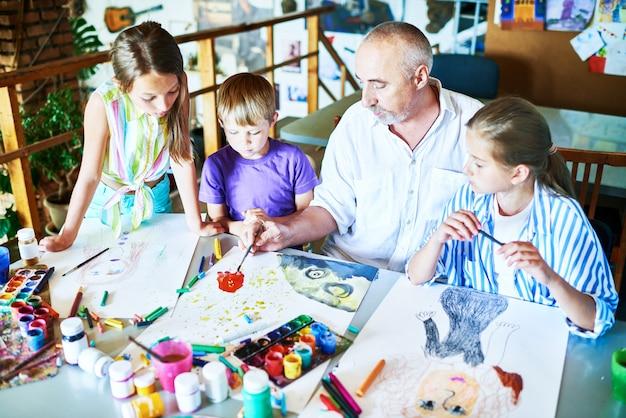 Dzieci malarstwo z nauczycielem w klasie sztuki