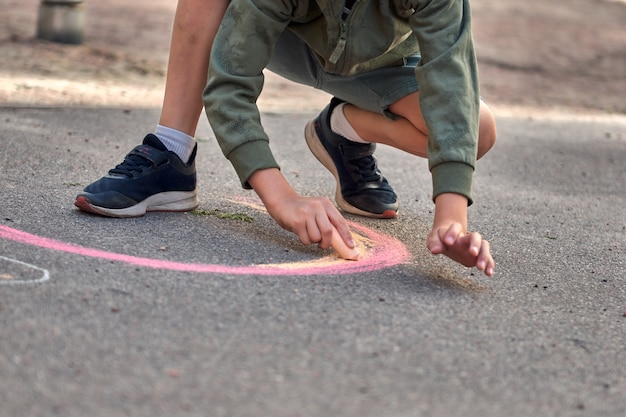 Dzieci malują na zewnątrz. chłopiec rysujący tęczową kredą na asfalcie plac zabaw