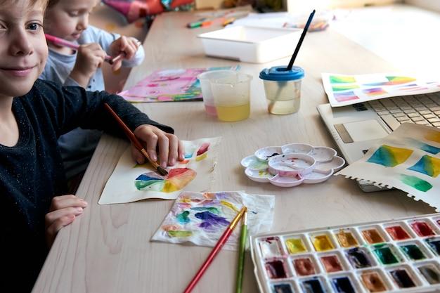 Dzieci malują obrazki farbami akwarelowymi podczas lekcji plastyki. uczniowie koncentrują się na rysowaniu pędzlem. koło kolorów akwareli i paleta. lekcje hobby dla początkujących z teorii kolorów