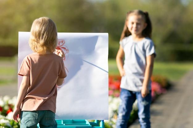Dzieci malują sobie nawzajem portrety.