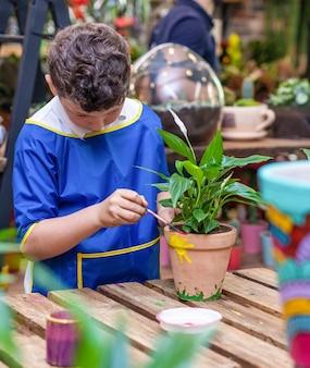 Dzieci malują z bliska rośliny doniczkowe z ceramiki