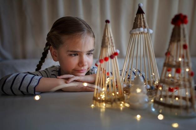 Dzieci marzą w pobliżu rzemieślniczej choinki z bambusowych patyczków ozdoba wielokrotnego użytku diy noworoczna dekoracja