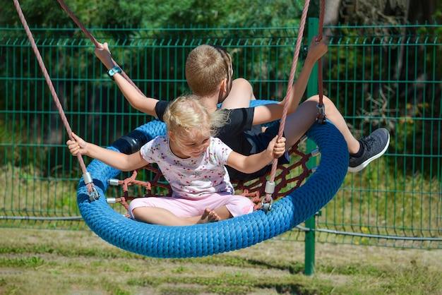 Dzieci na huśtawce chłopiec i dziewczynka jeżdżą na huśtawce w parku na letni dzień huśtawka w amu...