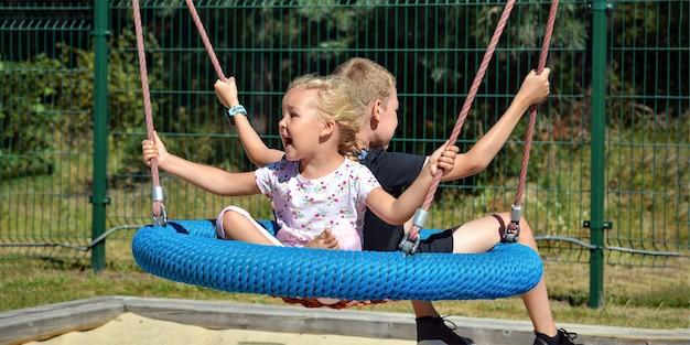 Dzieci na huśtawce. chłopiec i dziewczynka jeździć na huśtawce w parku w letni dzień. huśtawka w dziecięcym parku rozrywki. baner z miejscem na tekst