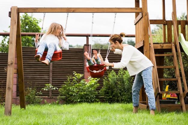 Dzieci na huśtawce. dziewczęce siostry kołyszą się na huśtawce na podwórku. letnia zabawa.