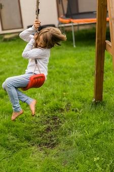 Dzieci na huśtawce. dziewczyna kołysząc się na huśtawce na podwórku. letnia zabawa.