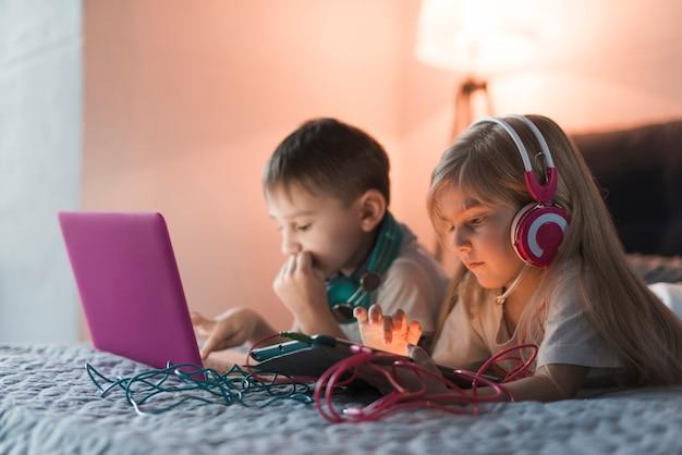 Dzieci na łóżku z laptopa i tabletu