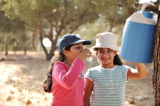 Dzieci na pikniku w obozie harcerskim w przyrodzie, dziewczyny pijące wodę