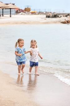 Dzieci na plaży morskiej. bliźniacy idą wzdłuż wody morskiej.