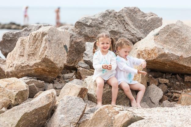 Dzieci na plaży morskiej. bliźniacy siedzą na kamienie i wodę morską.