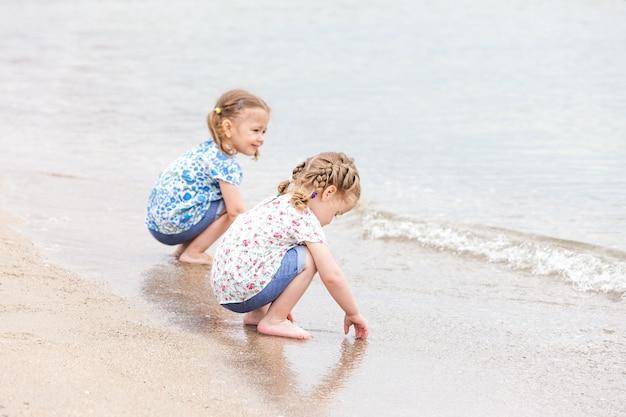 Dzieci na plaży morskiej. bliźniaki siedzą wzdłuż wody morskiej.
