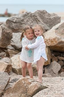 Dzieci na plaży morskiej. bliźniaki stojące przed kamieniami i wodą morską.