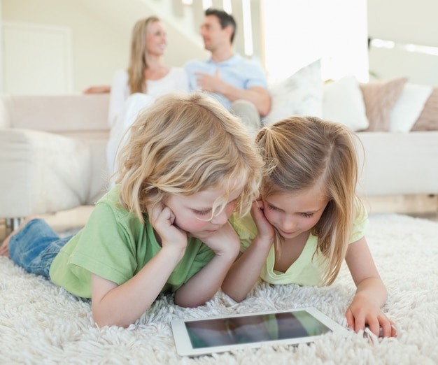 Dzieci na podłodze z tabletem i rodzicami za nimi