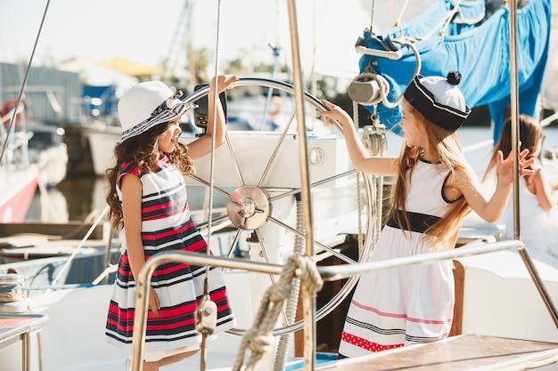 Dzieci na pokładzie jachtu do picia soku pomarańczowego. dziewczyny nastolatki lub dzieci przeciw błękitne niebo na zewnątrz. kolorowe ubrania. koncepcje mody dziecięcej, słonecznego lata, rzeki i wakacji.