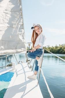 Dzieci na pokładzie jachtu do picia soku pomarańczowego. dziewczyny nastolatki lub dzieci przeciw błękitne niebo na zewnątrz. kolorowe ubrania.