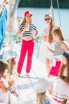 Dzieci na pokładzie jachtu do picia soku pomarańczowego. dziewczyny nastolatki lub dzieci przeciw błękitne niebo na zewnątrz