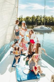 Dzieci na pokładzie jachtu do picia soku pomarańczowego. dziewczyny nastolatki lub dzieci przeciw błękitne niebo na zewnątrz.