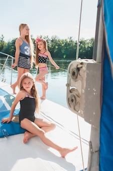 Dzieci na pokładzie jachtu morskiego. dziewczyny nastolatki lub dzieci przeciw błękitne niebo na zewnątrz