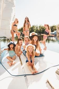Dzieci na pokładzie jachtu morskiego. nastolatki lub dzieci na zewnątrz. kolorowe ubrania. koncepcje mody dziecięcej, słonecznego lata, rzeki i wakacji.