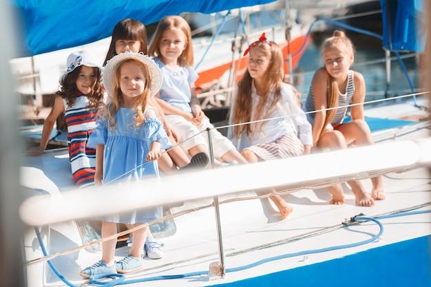 Dzieci na pokładzie morskiego jachtu piją sok pomarańczowy. nastolatki lub dzieci dziewczyny przeciw błękitne niebo na zewnątrz. kolorowe ubrania. koncepcje mody dziecięcej, słonecznego lata, rzeki i wakacji.