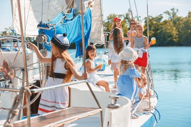 Dzieci na pokładzie morskiego jachtu piją sok pomarańczowy. nastolatki lub dzieci dziewczyny przeciw błękitne niebo na zewnątrz.