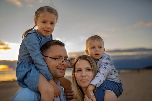 Dzieci na ramionach rodziców na plaży na koncepcji rodzinnych wakacji o zachodzie słońca