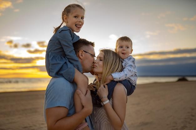 Dzieci na ramionach rodziców na plaży o zachodzie słońca mama i tata całują koncepcję wakacji rodzinnych