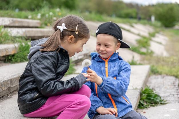 Dzieci na spacerze komunikują się i patrzą na kwiat.