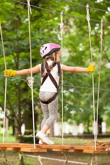 Dzieci na torze przeszkód w parku przygód w kasku górskim i sprzęcie ochronnym