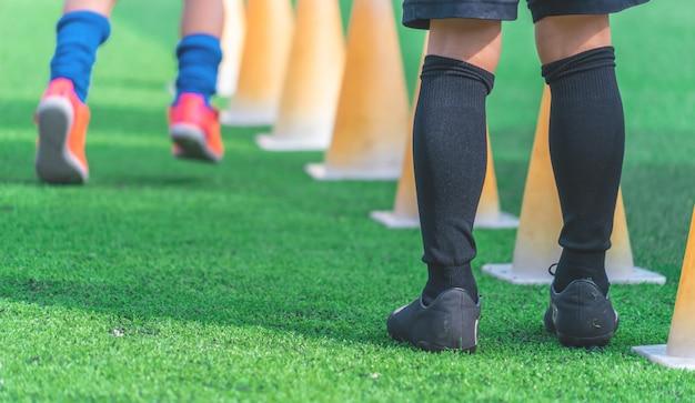 Dzieci na trening piłkarski na zielonym odkrytym boisku piłkarskim