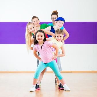 Dzieci na zajęciach zumby tańczą w nowoczesnej choreografii grupowej