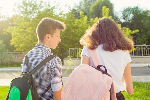 Dzieci nastolatki chodzą do szkoły, widok z tyłu