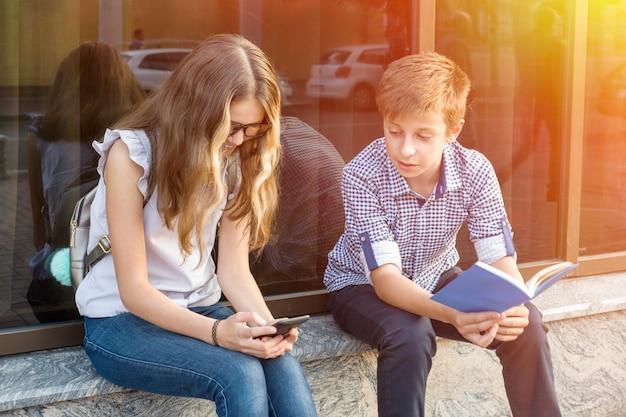 Dzieci nastolatki, czytając książkę i używając smartfona.