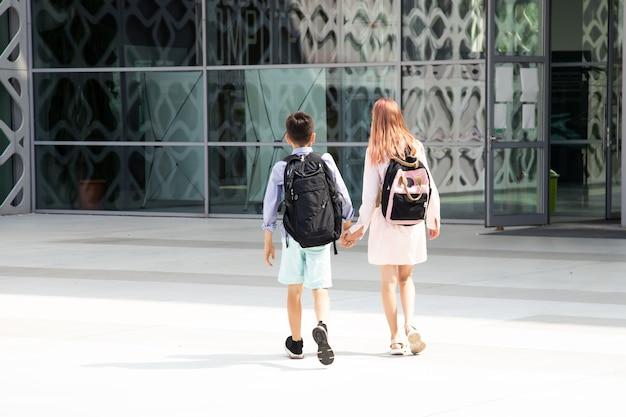 Dzieci nastolatki dzieci w wieku szkolnym chłopiec i dziewczynka lat na tle betonowej ściany z plecakami ...